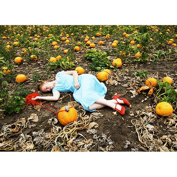 Frau liegt mit roten Fäden in Kürbisfeld