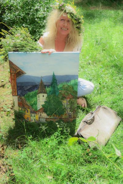 Künstlerin auf Wiese mit einem ihrer Bilder
