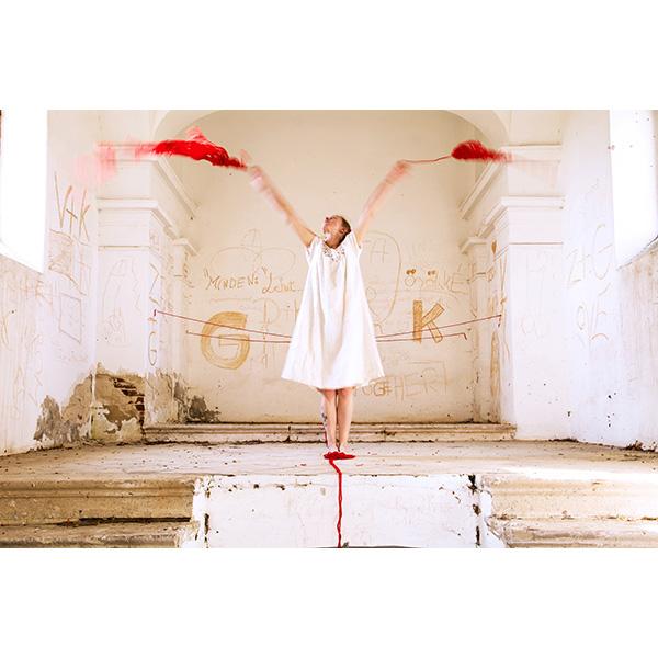 Frau in weiß verschüttet rote Fäden in weißem Raum
