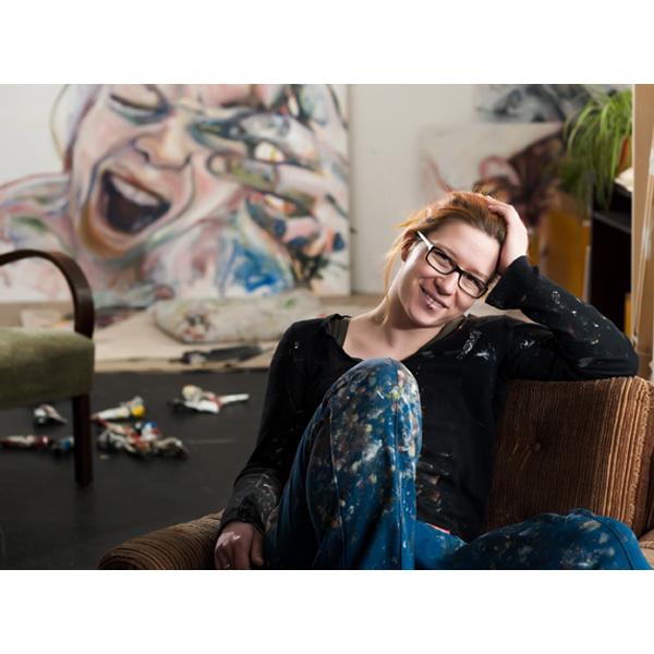 Judith Reßler auf der Couch vor einem ihrer Werke