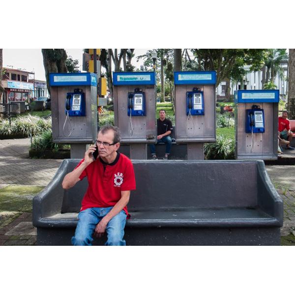 Mann telfoniert mit Handy vor 4 Telefonzellen