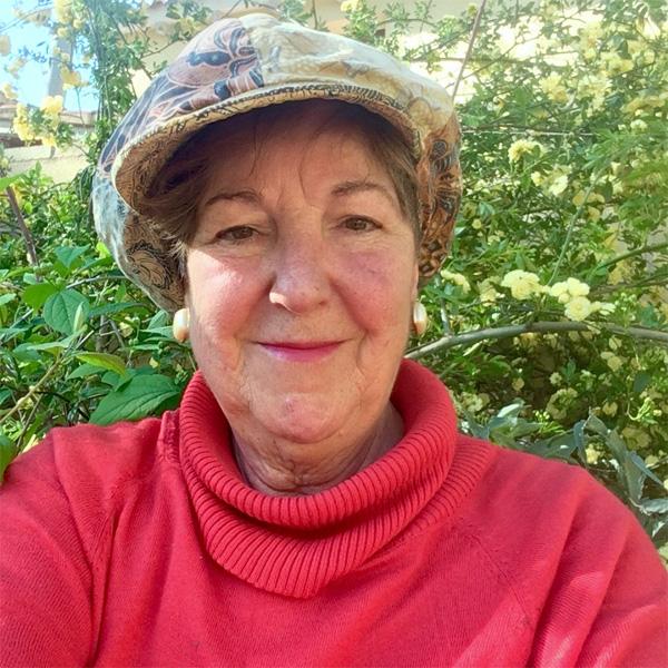 Carmen Marcos mit rotem Pullover und Mütze vor grünem Busch